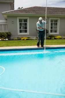 Senior man cleaning swimming pool on a sunny day