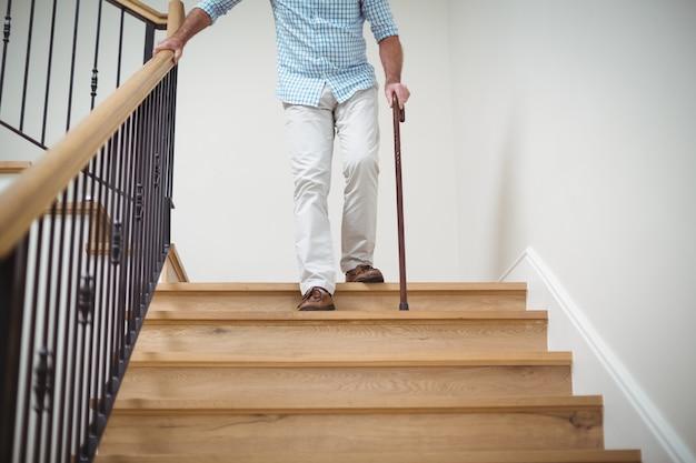 Senior man climbing downstairs with walking stick