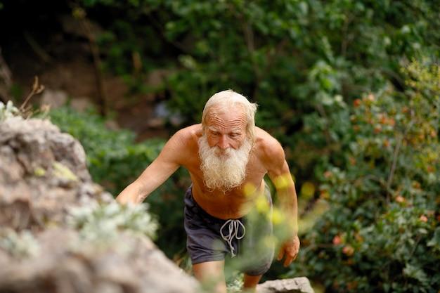 바위에 등반 하는 수석 남자. 긴 흰 수염을 가진 할아버지