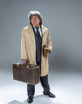 The senior man in cloak as detective or mafia boss.