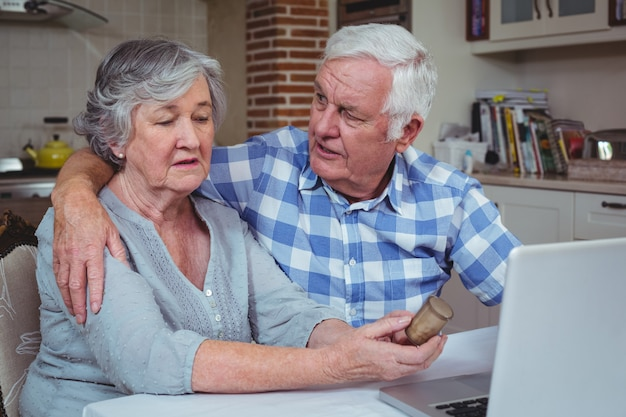 Senior man consoling wife holding pills container