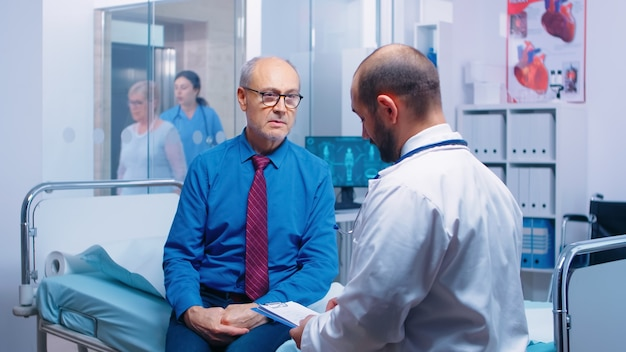 Senior man consulting with doctor sitting on hospital bed. ill aged patient seeking medical advice for disease prevention from general practitioner in modern private clinic, doctor diagnosis