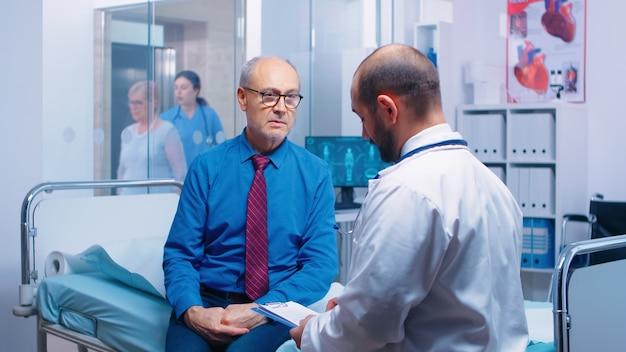 病院のベッドに座っている医師と相談する年配の男性。現代の民間クリニックで一般開業医から病気の予防のための医学的アドバイスを求めている病気の高齢患者、医師の診断