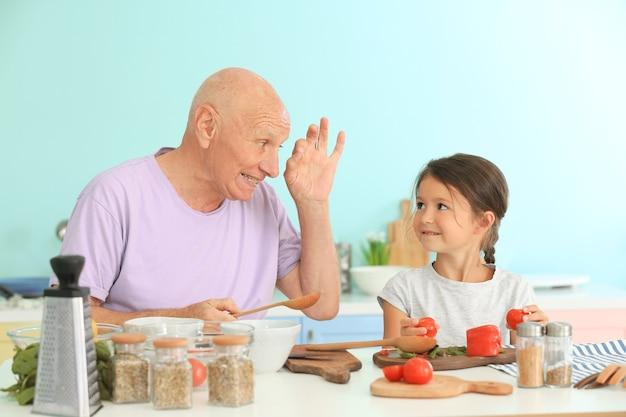 キッチンで孫娘と一緒に料理をする年配の男性