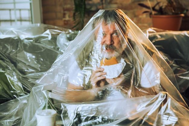 Старший мужчина, покрытый пластиком, ест фаст-фуд и пьет пиво, загрязнение окружающей среды людьми