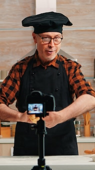 Senior man creating content for culinary blog, explaining the recipe step by step. retired blogger chef influencer using internet technology communicating on social media with digital equipment
