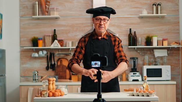 料理ブログのコンテンツを作成し、レシピを段階的に説明する年配の男性。ソーシャルメディア上でデジタル機器と通信するインターネット技術を使用する、引退したブロガーシェフのインフルエンサー