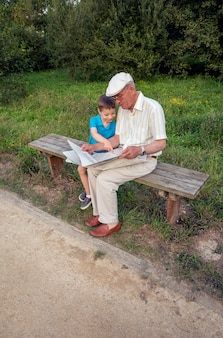 Senior man and cute child reading a newspaper sitting on park bench. two different generations concept.