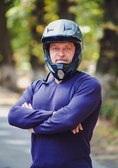 A senior man in dark helmet outdoor. casual clothes. crossed hands. blue sweater. outdoor blurred background. closeup.