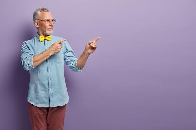 Senior man in denim shirt and yellow bowtie