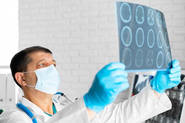 マスクの年配の男性医師が病院のクローズアップで頭のmriを検査します