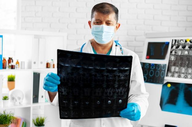Senior man doctor in mask examines head mri in hospital
