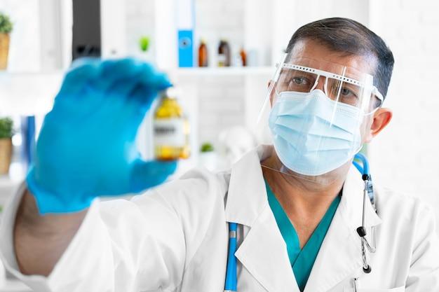 수석 남자 의사 또는 과학자 백신 유리 병을 들고