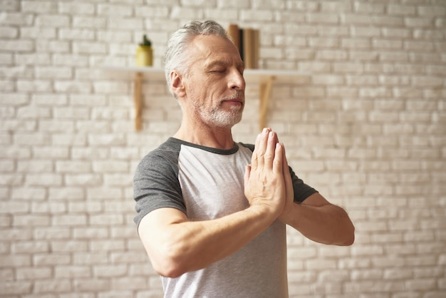 Senior man does yoga exercises with eyes closed.