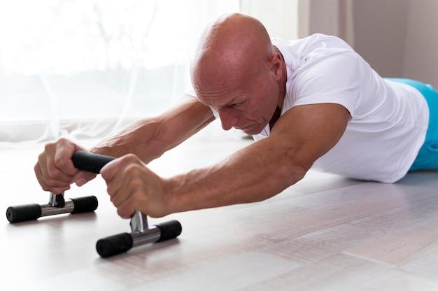 Старший мужчина делает упражнения в помещении