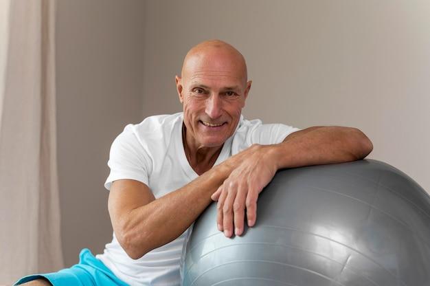 Старший мужчина делает упражнения с фитнес-мячом