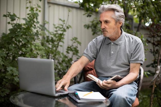 Senior man doing online classes on a laptop
