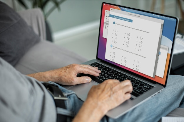ノートパソコンでオンラインクラスをやっている年配の男性