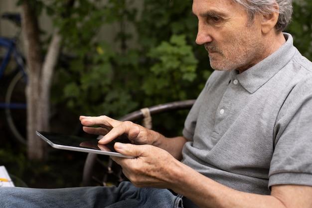 屋外でタブレットでオンラインクラスをやっている年配の男性