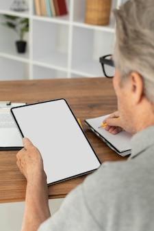タブレットでオンラインクラスをやっている年配の男性