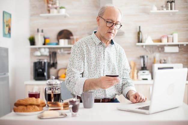 彼の台所から朝にオンライン購入をしている年配の男性。クレジットカードとラップトップからのアプリケーションを使用してオンラインで支払う年金受給者。でインターネット決済ホームバンク購入を使用して退職した高齢者