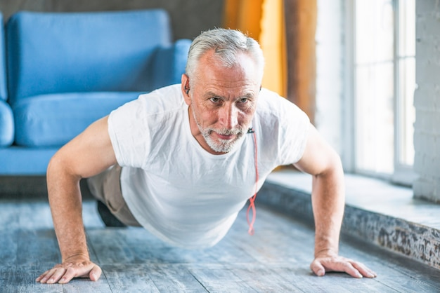 Senior man doing pushup at home