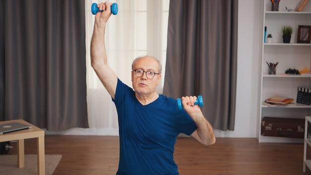 ダンベルを使用してリビングルームでスポーツをしている年配の男性。老人年金受給者が自宅でヘルスケアスポーツを健康的に訓練し、高齢者でフィットネス活動を行う