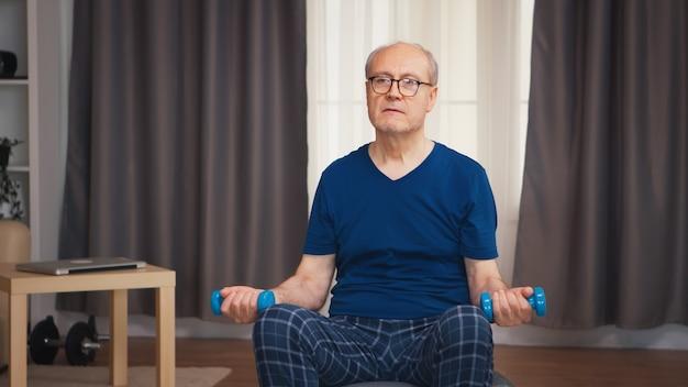 ダンベルで上腕二頭筋のトレーニングをしている年配の男性。老人年金受給者が自宅でヘルスケアスポーツを健康的に訓練し、高齢者でフィットネス活動を行う