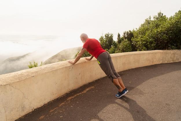屋外でストレッチや屈曲のスポーツエクササイズをしている年配の男性