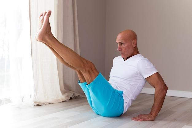 Старший мужчина делает упражнения на растяжку