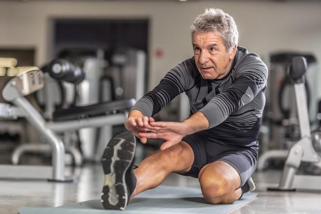 Старший мужчина делает растяжку в своей тренировочной одежде в окружении тренажеров в фитнес-центре.