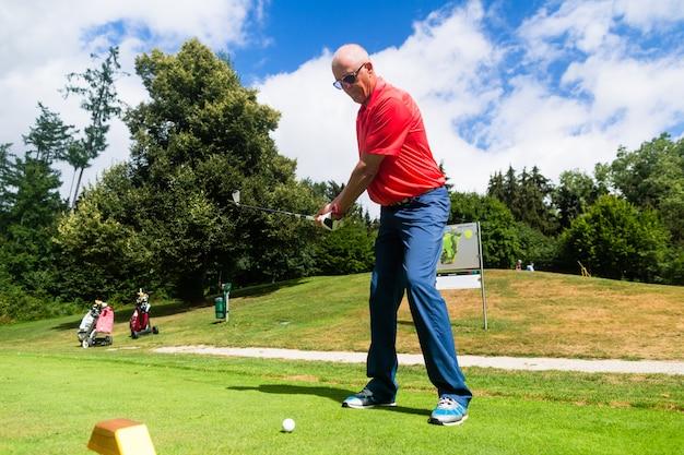 Senior man doing tee stroke on golf course