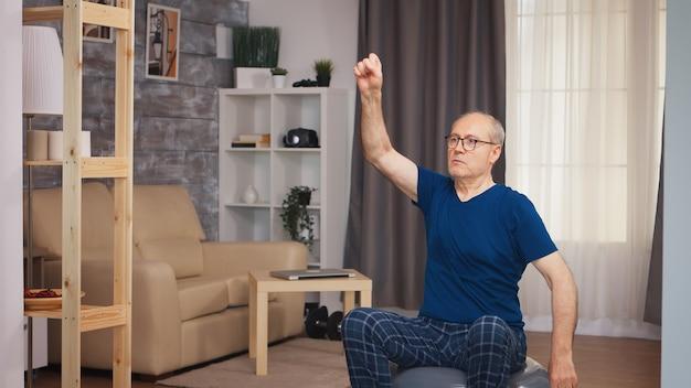 フィットネストレーニングの前にウォームアップ運動をしている年配の男性。老人年金受給者が自宅でヘルスケアスポーツを健康的に訓練し、高齢者でフィットネス活動を行う