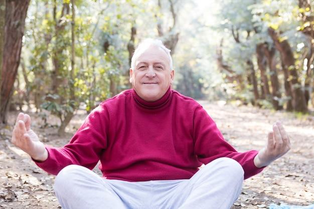 Uomo maggiore che fa yoga nel parco