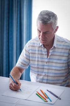 Senior man drawing in drawing book