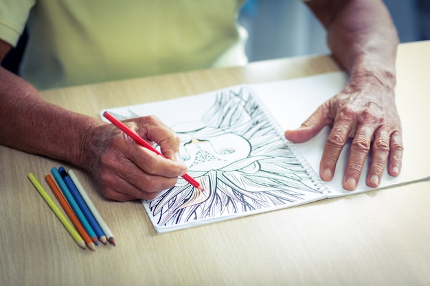 Senior man drawing with a colored pencil in drawing book