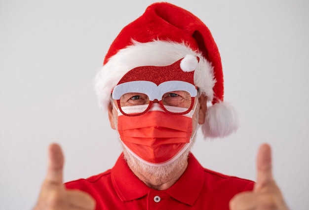 A senior man dressed in red as santa claus wearing a surgical mask due to the coronavirus and makes a sign of optimism. merry christmas at the time of the covid-19 virus.