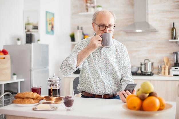 Ktichenで朝食時にコーヒーを飲み、スマートフォンを使用している年配の男性。