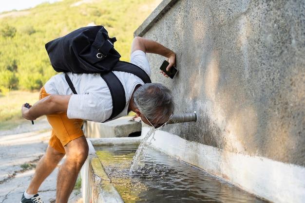 Старший мужчина пьет пресную воду