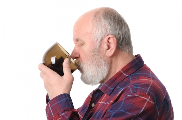 Senior man drinking from cup.