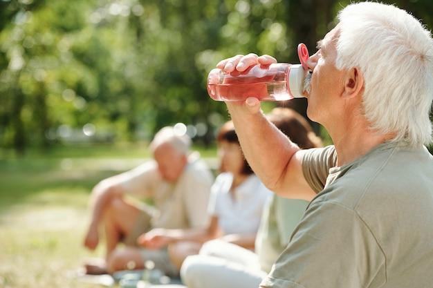 야외 공원에서 스포츠 훈련 후 병에서 물을 마시는 수석 남자