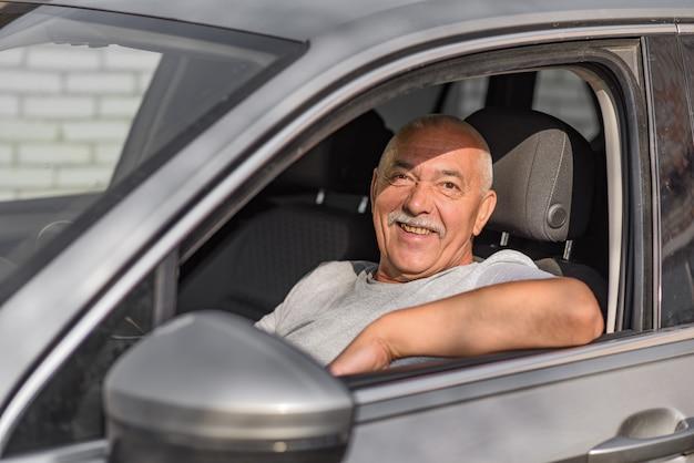 Старший мужчина за рулем автомобиля, глядя в камеру.