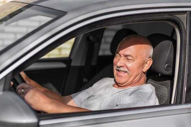 カメラを見ながら車を運転する年配の男性。
