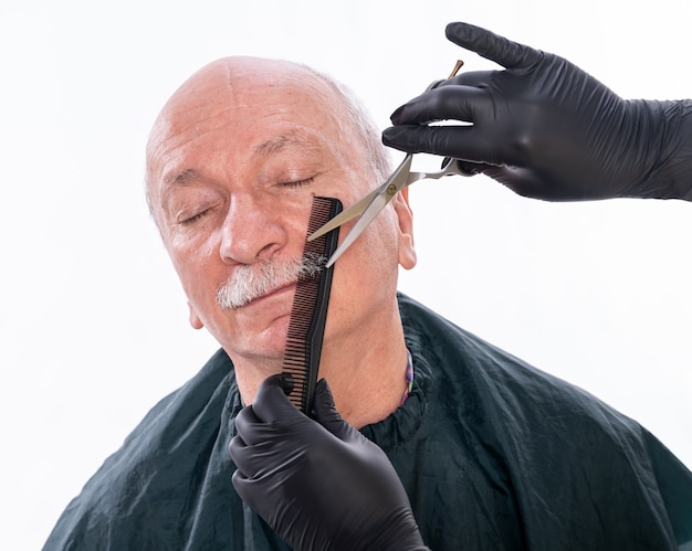 Senior man during moustache grooming process