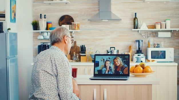 노트북을 사용하여 부엌에서 딸과 화상 회의를 하는 동안 수석 남자. 현대 통신 온라인 인터넷 웹 기술을 사용하는 노인.