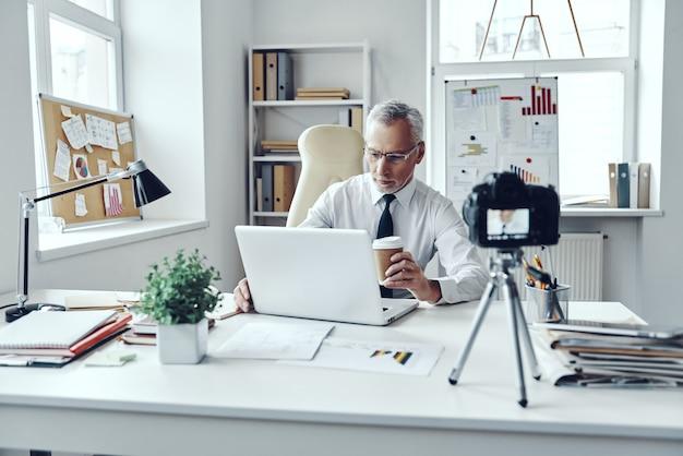 Senior man in elegant shirt and tie working using laptop while making social media video