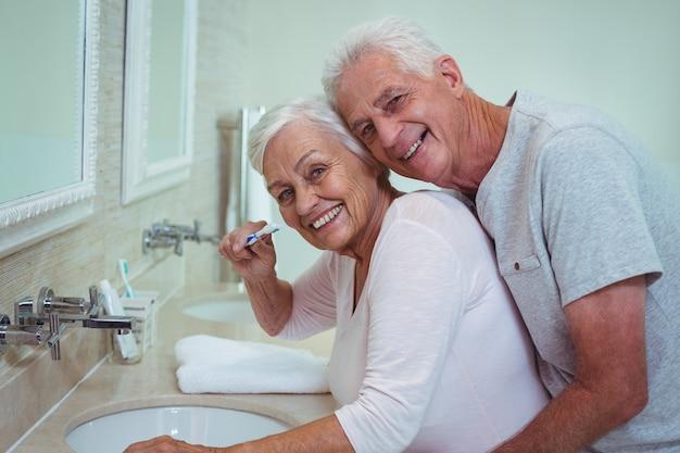 Senior man embracing wife brushing in bathroom