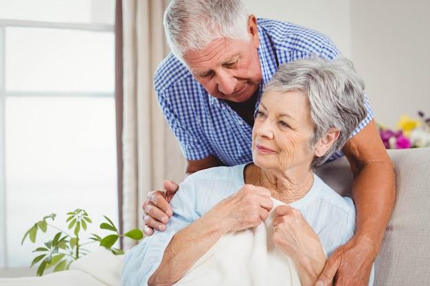 Senior man embracing woman in living room
