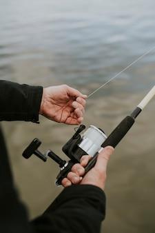 Старший мужчина наслаждается рыбалкой на берегу озера