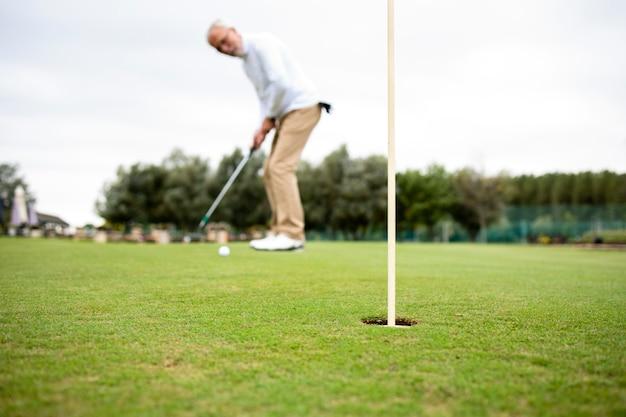 Старший мужчина наслаждается своим отдыхом на пенсии и играет в гольф.